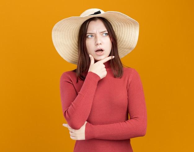 Impressionato giovane bella ragazza che indossa cappello da spiaggia tenendo la mano sul mento guardando a lato