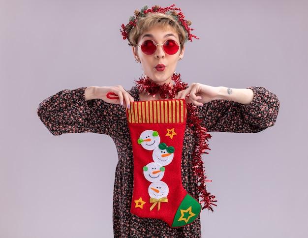 白い背景で隔離の側を見てクリスマスの靴下を保持しているメガネと首の周りにクリスマスのヘッドリースと見掛け倒しの花輪を身に着けている感動の若いかわいい女の子