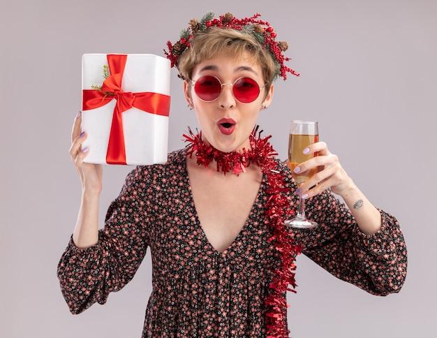 Впечатленная молодая красивая девушка в рождественском венке и гирлянде из мишуры на шее с бокалами, держащими подарочную упаковку и бокалом шампанского, смотрящую в камеру, изолированную на белом фоне