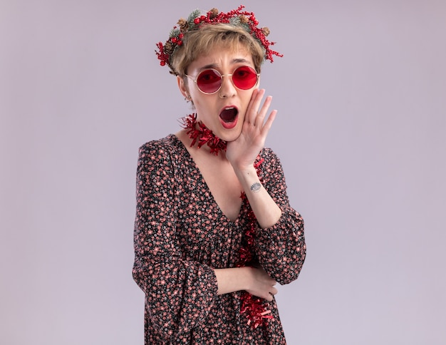 복사 공간이 흰 벽에 고립 된 사람에게 외치는 입 근처에 손을 유지하는 안경 목 주위에 크리스마스 머리 화환과 반짝이 화환을 입고 감동 젊은 예쁜 여자