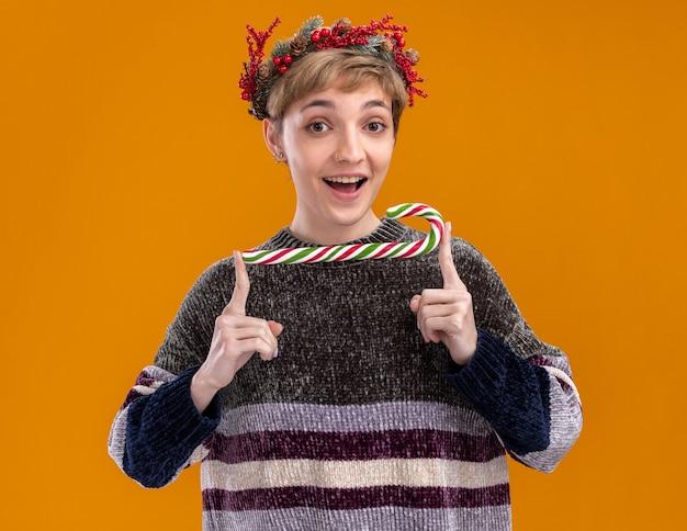 オレンジ色の背景で隔離のカメラを見てクリスマスの甘い杖を保持しているクリスマスのヘッドリースを身に着けている感動の若いかわいい女の子