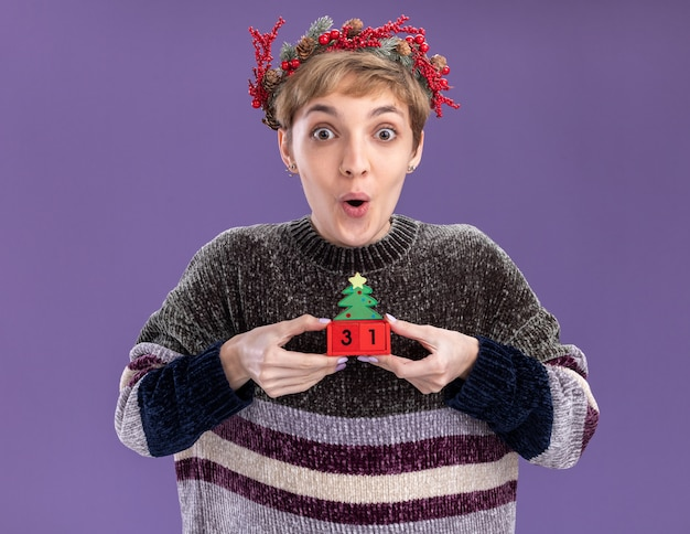 Impressed young pretty girl wearing christmas head wreath holding christmas tree toy with date looking at camera isolated on purple background