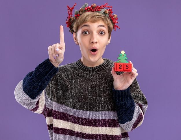 Impressionato giovane bella ragazza che indossa la corona della testa di natale che tiene il giocattolo dell'albero di natale con la data che guarda l'obbiettivo rivolto verso l'alto isolato su sfondo viola