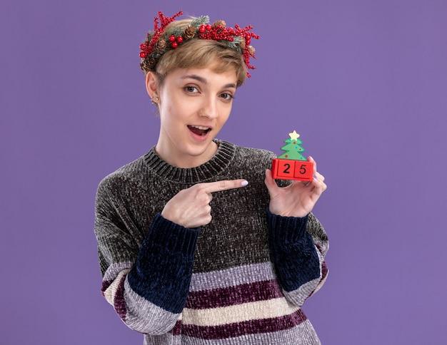 Впечатленная молодая красивая девушка в рождественском венке держит елочную игрушку с датой, указывая на нее, глядя в камеру, изолированную на фиолетовом фоне
