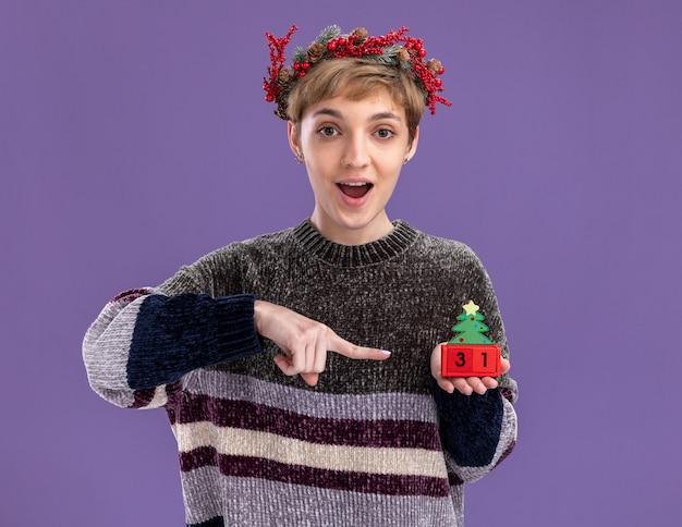 Impressionato giovane bella ragazza che indossa la corona della testa di natale che tiene il giocattolo dell'albero di natale con la data che indica esso che guarda l'obbiettivo isolato su fondo viola