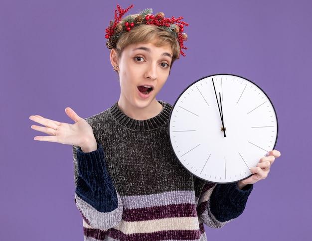 紫色の背景に分離された空の手を示すカメラを見て時計を保持しているクリスマスの頭の花輪を身に着けている感動の若いかわいい女の子