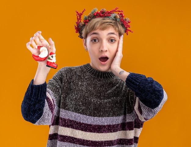 オレンジ色の背景で隔離のカメラを見て顔に手を保ちながらサンタクロースのクリスマスの飾りを保持しているクリスマスの頭の花輪を身に着けている感動の若いかわいい女の子
