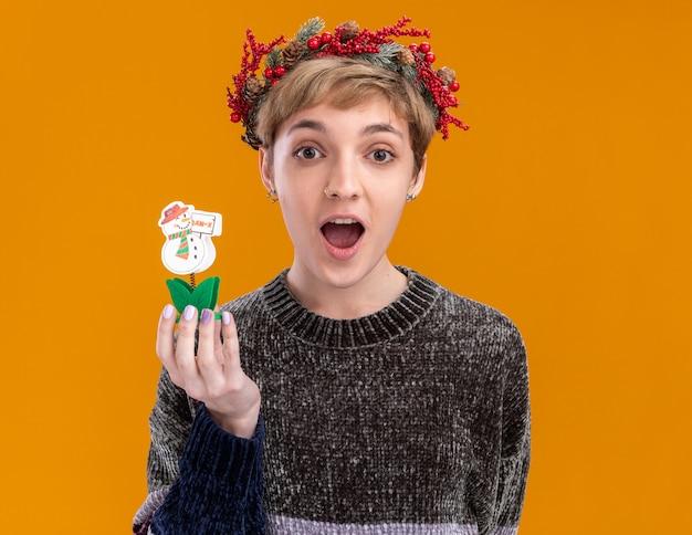 Impressionato giovane bella ragazza che indossa la corona della testa di natale che tiene il giocattolo del pupazzo di neve che guarda l'obbiettivo isolato su priorità bassa arancione