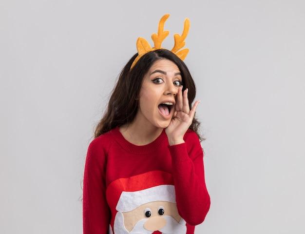 トナカイの角のヘッドバンドとささやくように見えるサンタクロースのセーターを着ている感動の若いかわいい女の子