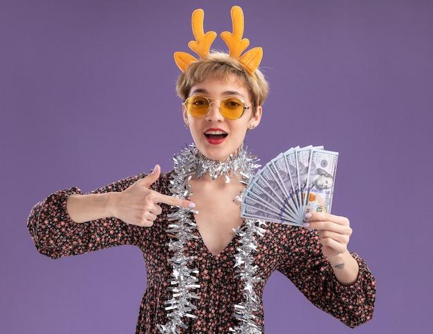 순록 뿔 머리띠와 안경을 들고 보라색 벽에 고립 된 돈을 가리키는 목 주위에 반짝이 갈 랜드를 입고 감동 젊은 예쁜 여자