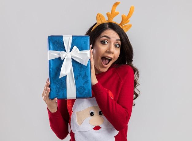 Impressionato giovane bella ragazza che indossa la fascia di corna di renna e maglione di babbo natale che tiene il pacchetto regalo di natale alla ricerca