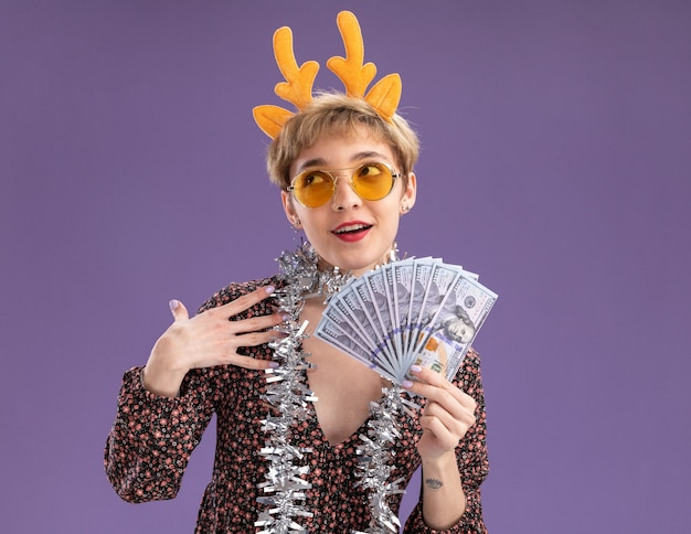 Impressed young pretty girl wearing reindeer antlers headband and tinsel garland around neck with glasses holding money looking up touching shoulder isolated on purple wall with copy space