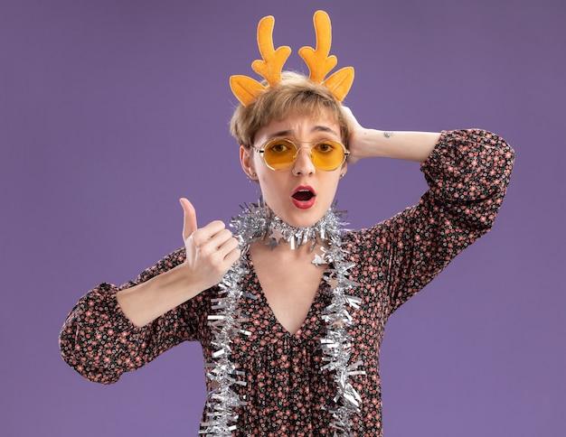Impressionato giovane bella ragazza che indossa la fascia di corna di renna e la ghirlanda di orpelli intorno al collo con gli occhiali che guarda l'obbiettivo tenendo la mano sulla testa che mostra il pollice in alto isolato su sfondo viola