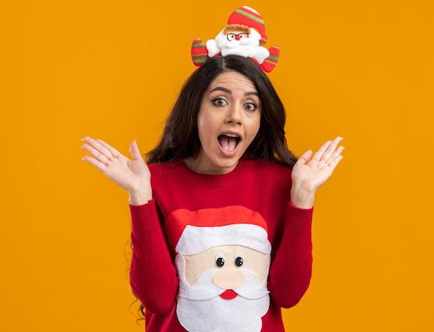 산타 클로스 머리띠와 스웨터를 입고 감동 젊은 예쁜 여자 빈 손을 보여주는 찾고