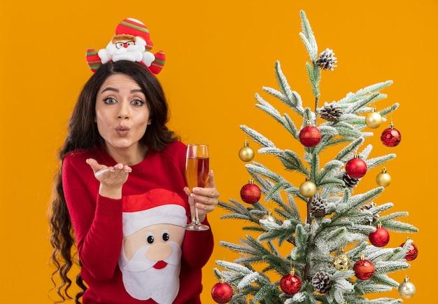 オレンジ色の背景に分離されたブローキスを送信するカメラを見てシャンパンのガラスを保持している装飾されたクリスマスツリーの近くに立っているサンタクロースのヘッドバンドとセーターを着ている感動の若いかわいい女の子