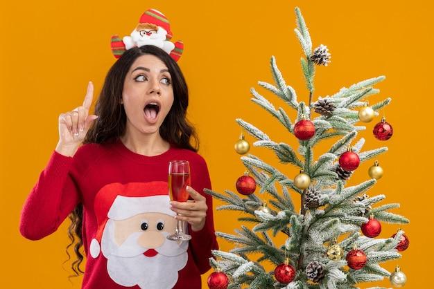 Впечатленная молодая красивая девушка в повязке на голову санта-клауса и свитере, стоящая возле украшенной рождественской елки с бокалом шампанского, смотрящая в сторону, указывающую вверх, изолирована на оранжевом фоне