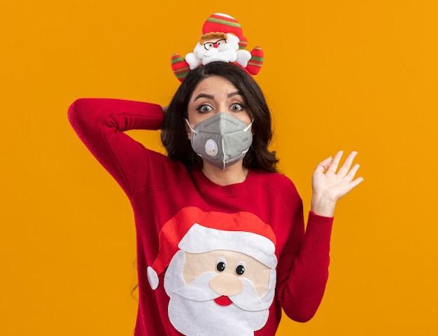 오렌지 배경에 고립 된 빈 손을 보여주는 카메라를보고 머리 뒤에 손을 유지 보호 마스크와 산타 클로스 머리띠와 스웨터를 입고 감동 젊은 예쁜 여자