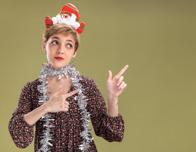 산타 클로스 머리띠와 목 주위에 반짝이 갈 랜드를 입고 인상적인 젊은 예쁜 여자를보고 올리브 녹색 배경에 고립 된 측면을 가리키는