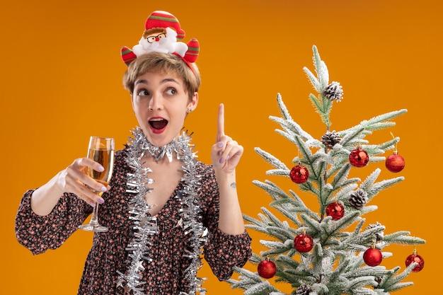 サンタ クロースのカチューシャと見掛け倒しの花輪を身に着けている美しい若い女の子が飾られたクリスマス ツリーの近くに立って、オレンジ色の壁に孤立した上向きの側を見てシャンパンのガラス