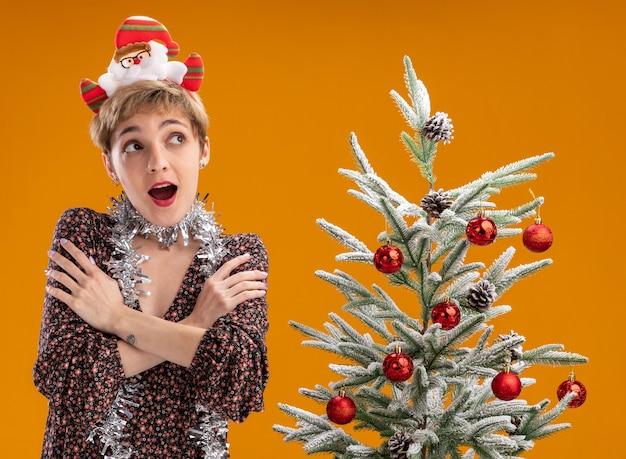 サンタ クロースのカチューシャと見掛け倒しの花輪を着て、飾られたクリスマス ツリーの近くに立って、オレンジ色の壁に隔離された側を見て腕を組んでいる、感銘を受けた若いかわいい女の子