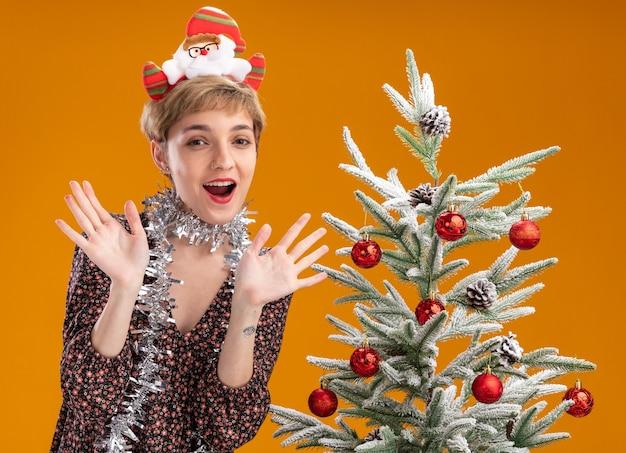 Впечатленная молодая красивая девушка в ободке санта-клауса и гирлянде из мишуры на шее, стоящая возле украшенной елки, показывая пустые руки, изолированные на оранжевом фоне