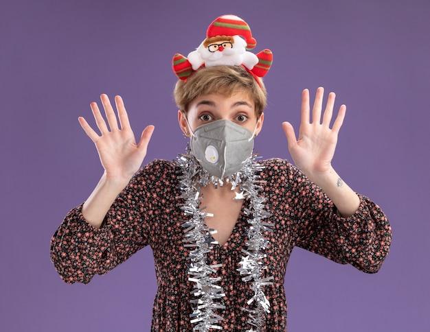 보라색 배경에 고립 손으로 10을 보여주는 카메라를보고 보호 마스크와 목 주위에 산타 클로스 머리띠와 반짝이 갈 랜드를 입고 감동 젊은 예쁜 여자