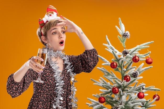 Impressionata giovane bella ragazza che indossa la fascia di babbo natale e una ghirlanda di orpelli intorno al collo in piedi vicino all'albero di natale decorato con in mano un bicchiere di champagne guardando il lato in lontananza isolato sul muro arancione