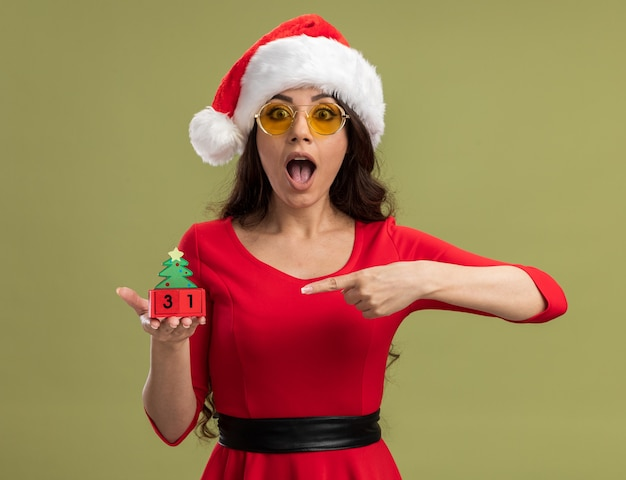 산타 모자와 안경을 착용하고 날짜를 찾고 크리스마스 트리 장난감을 가리키는 감동 된 젊은 예쁜 여자
