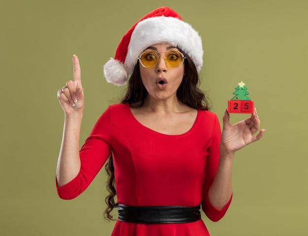 サンタの帽子とメガネを身に着けている感動の若いかわいい女の子は、オリーブグリーンの背景に分離された上向きのカメラを見て日付とクリスマスツリーのおもちゃを保持