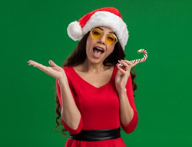 Impressionato giovane ragazza carina che indossa cappello santa e bicchieri tenendo il bastoncino di zucchero di natale guardando la telecamera che mostra la mano vuota isolata su sfondo verde