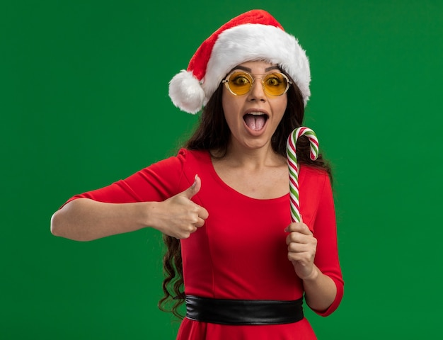 Impressionato giovane ragazza graziosa che indossa il cappello della santa e vetri che tengono il bastoncino di zucchero di natale che guarda l'obbiettivo che mostra pollice su isolato su fondo verde