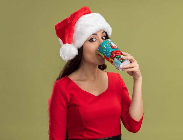 クリスマスのコーヒーカップを保持しているサンタの帽子をかぶって、オリーブグリーンの背景で隔離のコーヒーを飲むカメラを見て感動した若いかわいい女の子