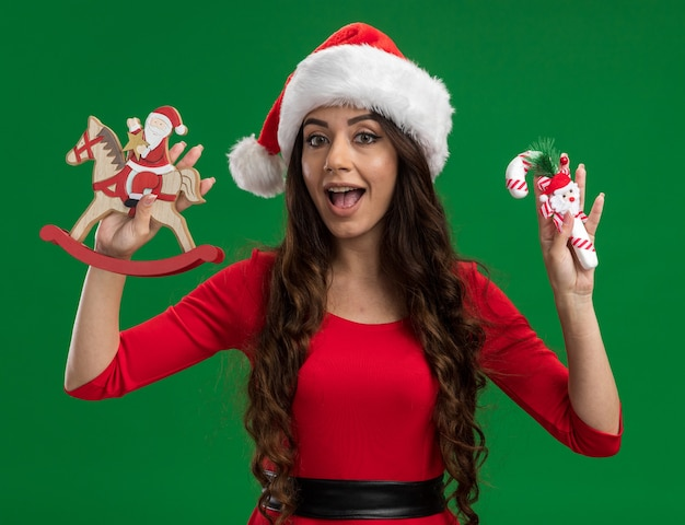 Impressed young pretty girl wearing santa hat holding santa on rocking horse figurine and candy cane ornament looking at camera isolated on green background