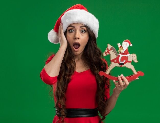 Impressed young pretty girl wearing santa hat holding santa on rocking horse figurine looking at camera keeping hand on head isolated on green background