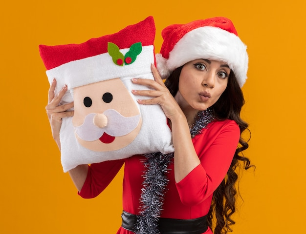 Impressionato giovane bella ragazza che indossa cappello da babbo natale e ghirlanda di orpelli intorno al collo tenendo il cuscino di babbo natale guardando camrea da dietro increspando le labbra isolate sul muro arancione