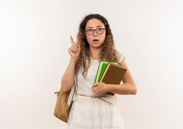 안경과 흰색에 고립 된 손가락을 올리는 책을 들고 다시 가방을 입고 감동 젊은 예쁜 여학생