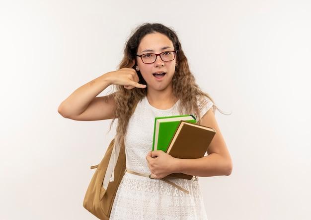 白で隔離の呼び出しジェスチャーを行う本を保持している眼鏡とバックバッグを身に着けている感動の若いかわいい女子高生