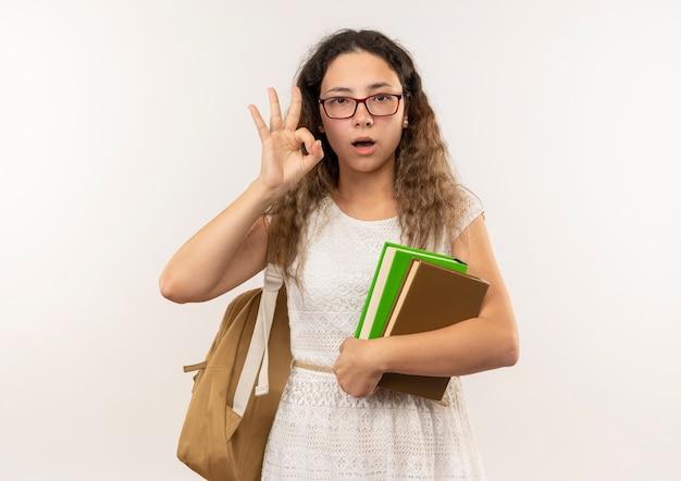 안경을 착용하고 흰색에 고립 된 확인 서명을하고 책을 들고 다시 가방을 입고 감동 젊은 예쁜 여학생