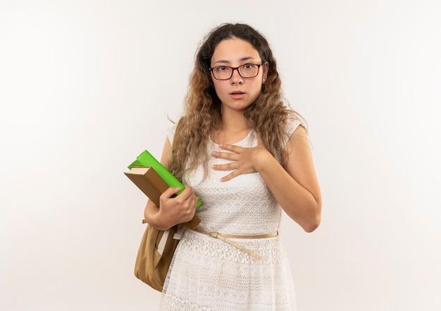 Впечатленная молодая симпатичная школьница в очках и задней сумке, держащая книги, положив руку на грудь, изолированную на белом