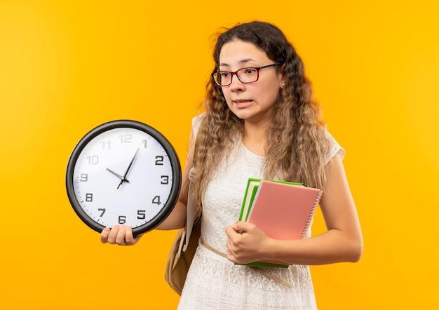 黄色で隔離された側を見て時計のメモ帳と本を保持している眼鏡とバックバッグを身に着けている感動の若いかわいい女子高生