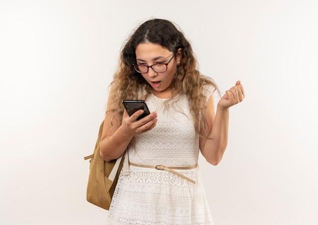 Impressionato giovane studentessa graziosa con gli occhiali e borsa posteriore che tiene e guardando il telefono cellulare stringendo il pugno isolato su bianco