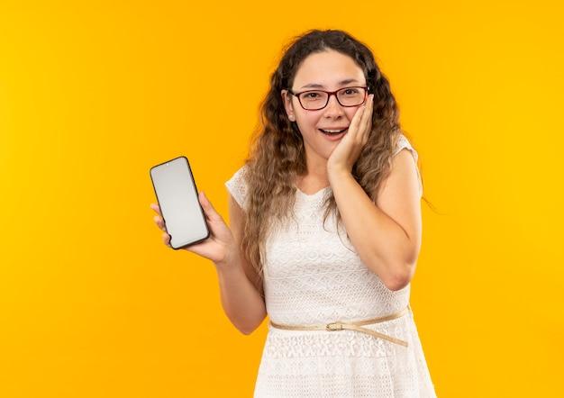 Impressionato giovane studentessa graziosa con gli occhiali e borsa posteriore che tiene il telefono cellulare che mette la mano sulla guancia isolata su colore giallo