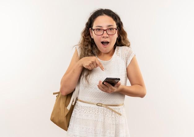 Impressionato giovane studentessa graziosa con gli occhiali e borsa posteriore che tiene e che indica al telefono cellulare isolato su bianco