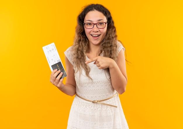 Impressionato giovane studentessa graziosa con gli occhiali tenendo e indicando biglietti aerei e carta di credito isolati su giallo