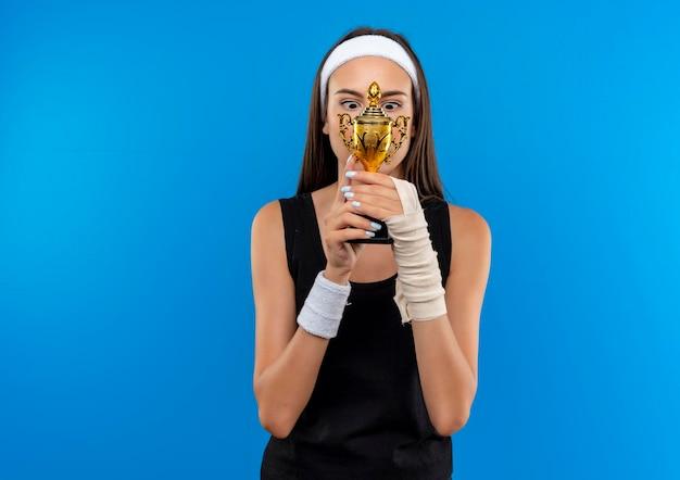 Впечатленная молодая симпатичная спортивная девушка с головной повязкой и браслетом, держащая и смотрящая на кубок победителя, с поврежденным запястьем и перевязанной повязкой, изолированной на синей стене с копией пространства