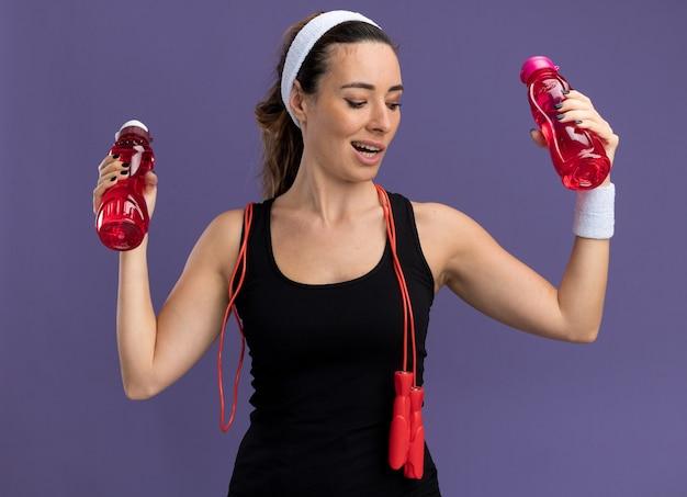 Впечатленная молодая симпатичная спортивная девушка с повязкой на голову и браслетами, держащая бутылки с водой, смотрит вниз со скакалкой на шее