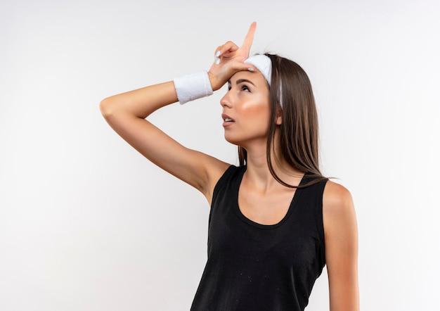 Impressionata giovane ragazza piuttosto sportiva che indossa fascia e cinturino che punta e guarda in alto sul muro bianco