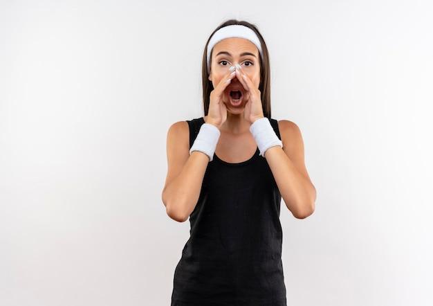 Impressionato giovane ragazza abbastanza sportiva che indossa fascia e cinturino che grida ad alta voce con le mani intorno alla bocca isolata sul muro bianco con spazio di copia