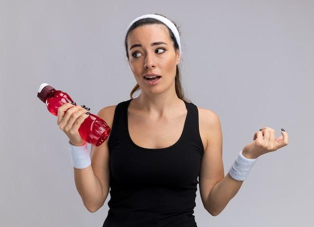 Impressionato giovane ragazza abbastanza sportiva che indossa fascia e braccialetti che tengono una bottiglia d'acqua guardando il lato tenendo la mano in aria isolata sul muro bianco