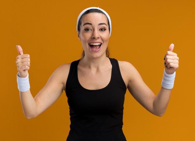 Impressionata giovane ragazza piuttosto sportiva che indossa fascia e braccialetti che mostrano i pollici in su isolati sul muro arancione